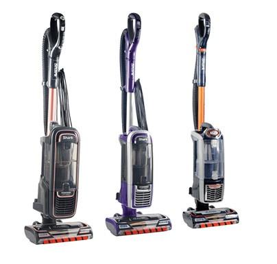 Three standing Shark vacuum cleaners